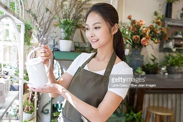 Female florist watering plants in flower shop