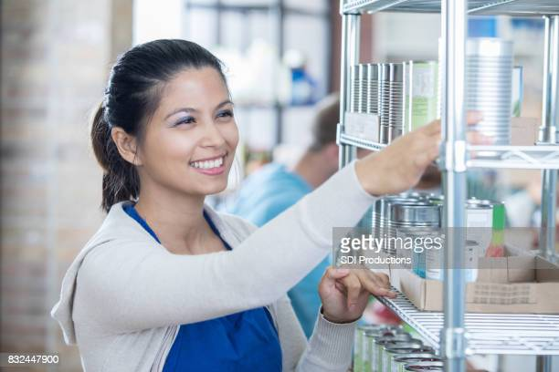 Female food bank volunteer checks expiration dates on canned goods