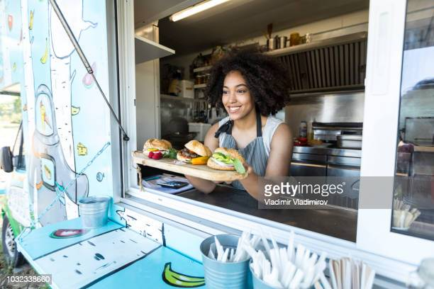 female food vendor offering sandwiches in food van - food truck stock photos and pictures
