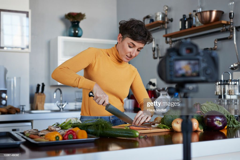 Female food vlogger making video while prepping vegetables in kitchen : Foto de stock