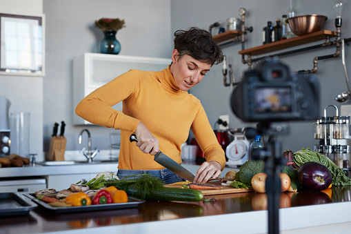 Female food vlogger making video while prepping vegetables in kitchen - gettyimageskorea