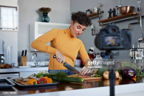 female food vlogger making video while prepping vegetables in kitchen - chop stock pictures, royalty-free photos & images