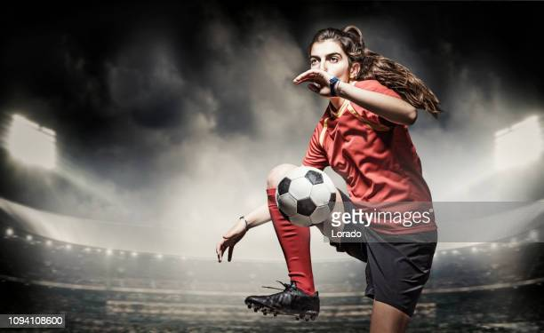 female football player controlling a soccer ball in front of stadium lights - team captain stock pictures, royalty-free photos & images