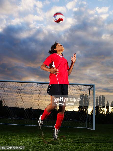 female football player (10-11) jumping and heading ball in pitch - heading stock pictures, royalty-free photos & images