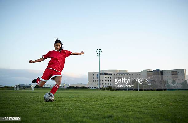 Female football player striking the ball on field