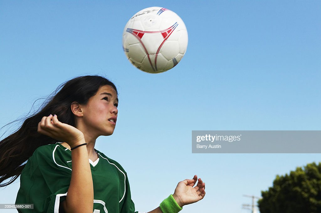 Female footballer (11-13) heading ball, low angle view : Stock Photo