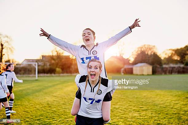Female footballer on friends back, celebrating