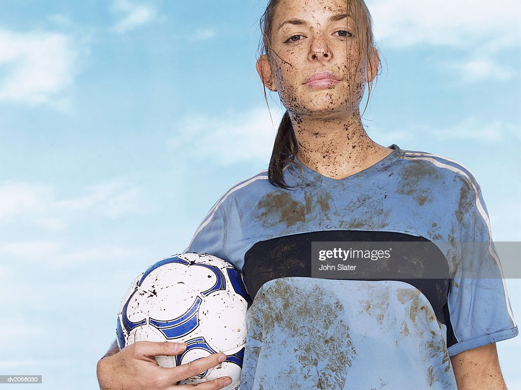 Female Footballer Splattered with Mud and Holding a Football : Stock Photo