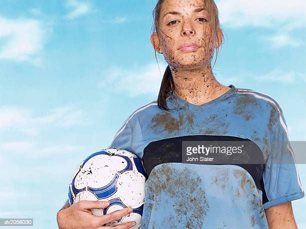 female footballer splattered with mud and holding a football - fußballtrikot stock-fotos und bilder
