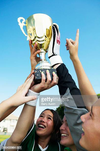 female footballers (13-15) holding up trophy, smiling - teen awards foto e immagini stock