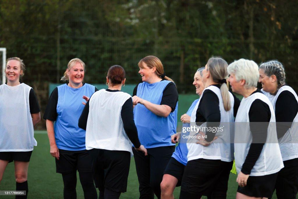 Female footballers smile during training : Stock Photo