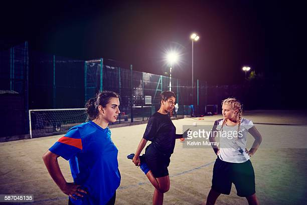 female footballers stretch in training session - sports training stock pictures, royalty-free photos & images