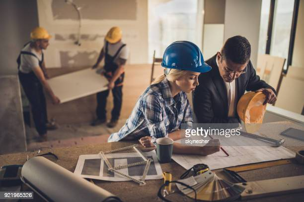 Female foreman and male architect analyzing blueprints at construction site.