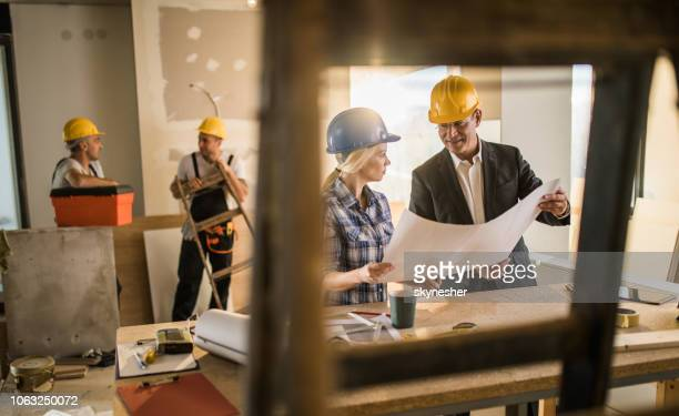 female foreman and male architect communicating while analyzing blueprints at construction site. - rebuilding stock pictures, royalty-free photos & images