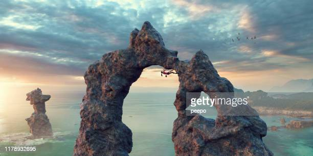 female free climber extreme climb on rock arch near sea - extreme sports stock pictures, royalty-free photos & images