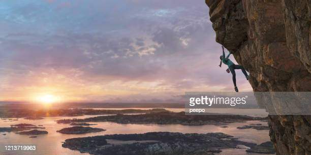 female free climber scaling steep coastal rock face at dawn - hanging stock pictures, royalty-free photos & images