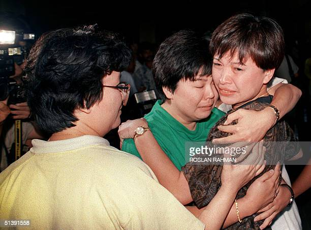 A female freed passengers from the hijacked Singapore Airlines Airbus receive a hug from a relative at Singapore's Changi International Airport 27...