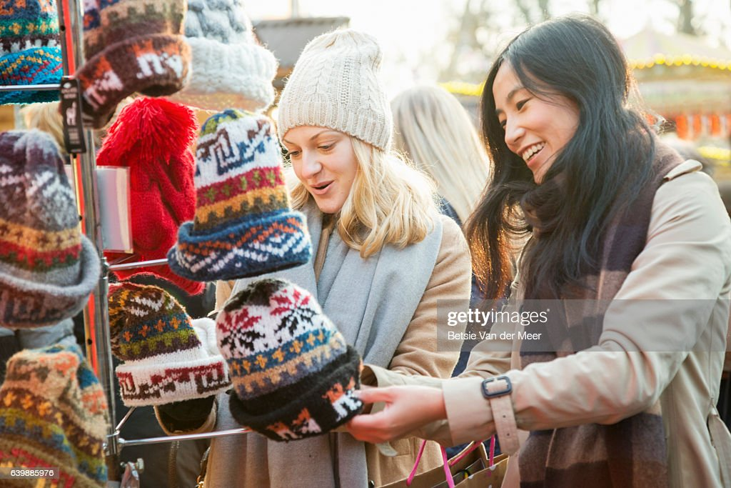 Female friends are looking at woolen hats at outdoor Christmas market stall. : Stock Photo