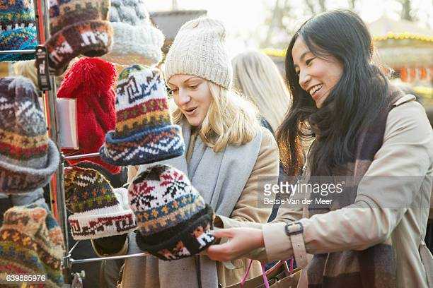 Female friends are looking at woolen hats at outdoor Christmas market stall.