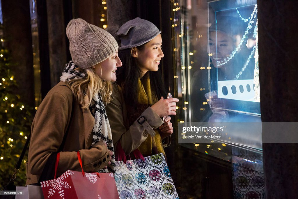 Female friends are looking into jewelry shop window at night time. : Stock Photo