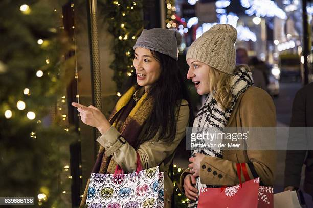 Female friends are looking into shopwindow while carrying christmas shopping bags.