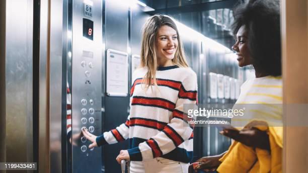 amigas que chegam no hotel - elevador - fotografias e filmes do acervo
