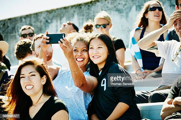 Female friends at soccer match taking selfie