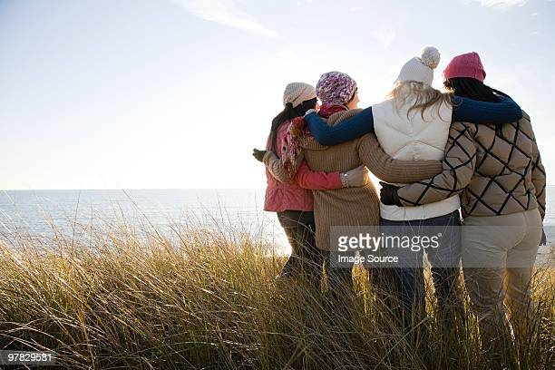 female friends by the sea - arm around stock pictures, royalty-free photos & images