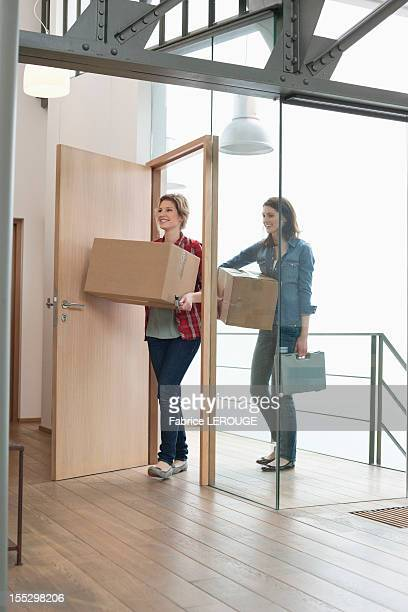 Female friends carrying cardboard boxes at home