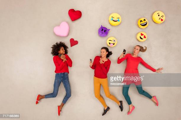 Female friends chatting and gossiping with emojies over their heads