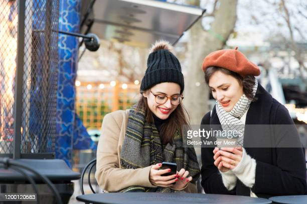 female friends checking phone in outdoor cafe. - hat stock pictures, royalty-free photos & images