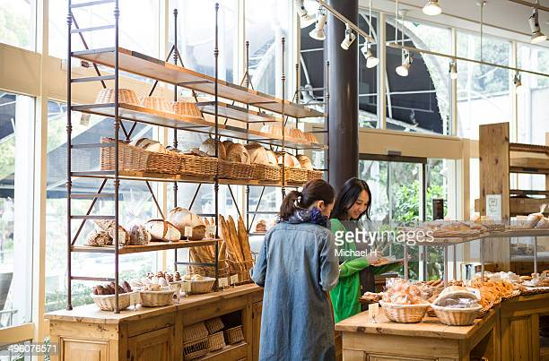 Female friends chosing breads in bakeryshop.