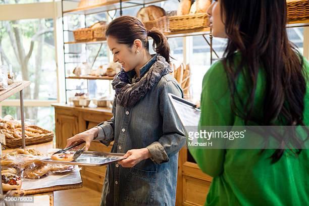 female friends chosing breads in bakeryshop. - パン屋 ストックフォトと画像