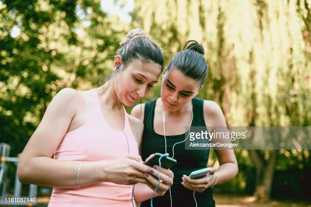 female friends comparing exercise playlists - colors soundtrack stock pictures, royalty-free photos & images