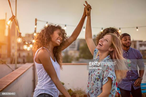 female friends dancing during party on terrace - dancing stock photos and pictures
