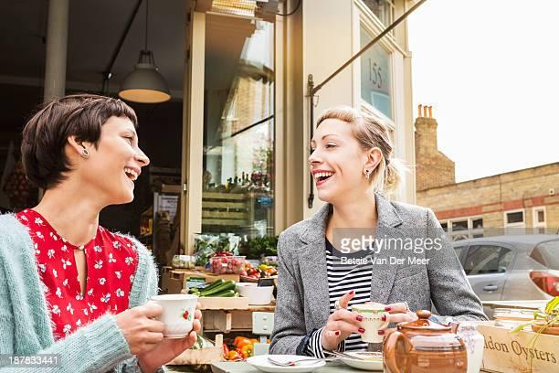 Female friends drinking tea outside farm shop.