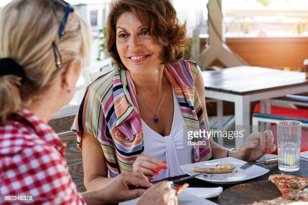 Female friends eating pizza in cafe