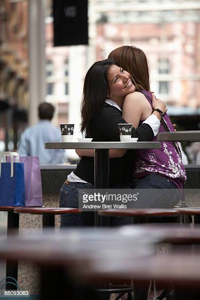 female friends embracing at city centre cafe - leeds city centre stock photos and pictures