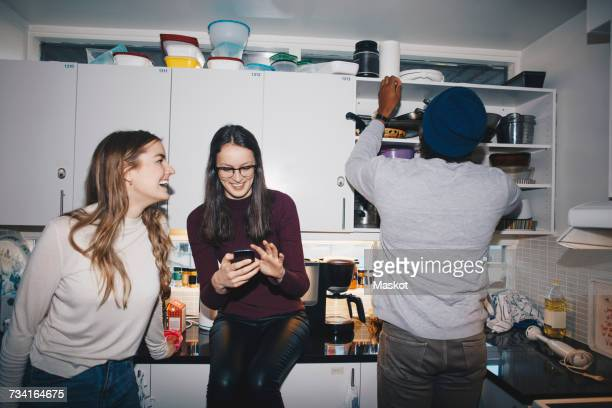 Female friends enjoying by man in kitchen at college dorm