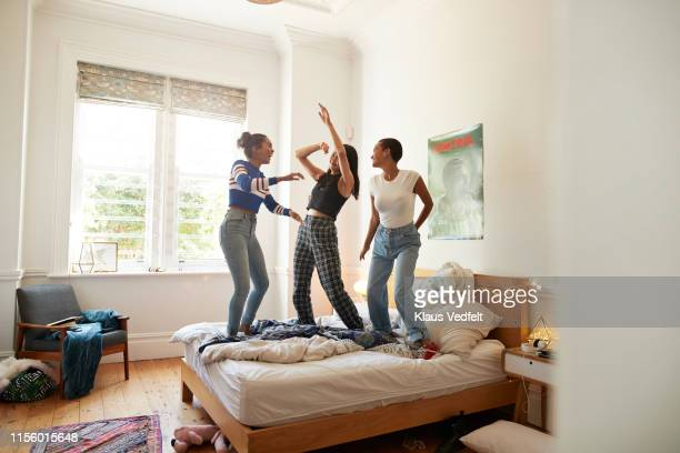 female friends enjoying while dancing on bed - slumber party stock pictures, royalty-free photos & images