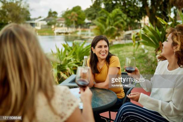 female friends enjoying wine and beer outdoors in afternoon - celebration fl stock pictures, royalty-free photos & images