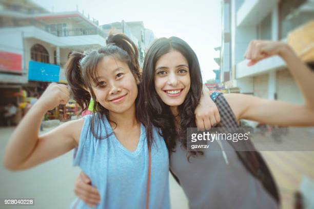 Female friends flexing muscles together on city roadside.