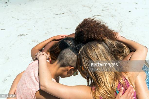Female friends forming huddle at beach