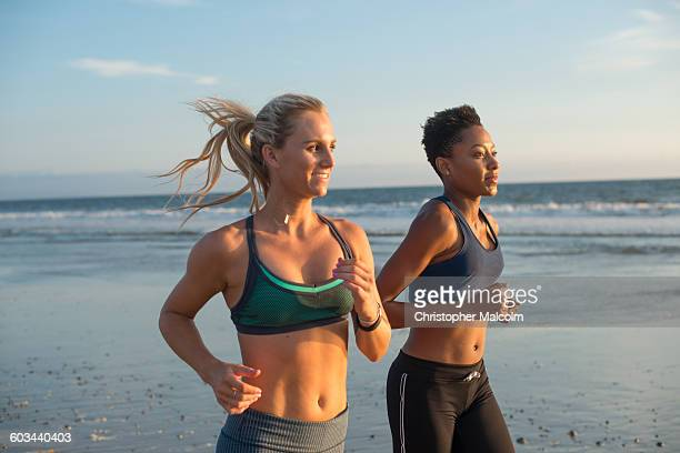 female friends go for run at the beach - sports bra stock pictures, royalty-free photos & images
