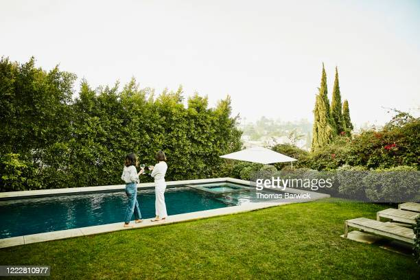 female friends hanging out by pool in backyard - women in see through tops stock pictures, royalty-free photos & images