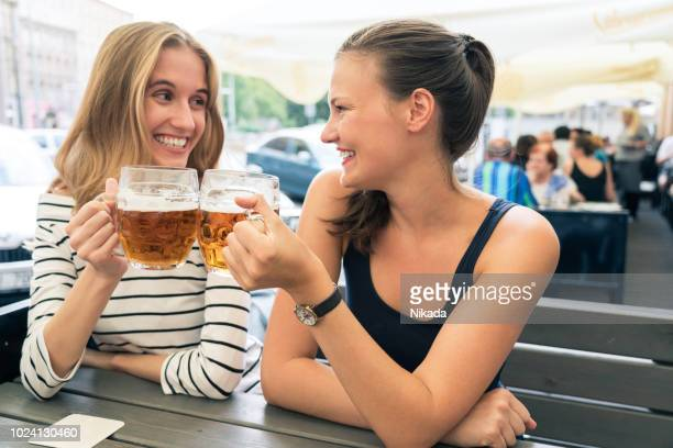 female friends having beers at outdoors cafe - bohemia czech republic stock pictures, royalty-free photos & images