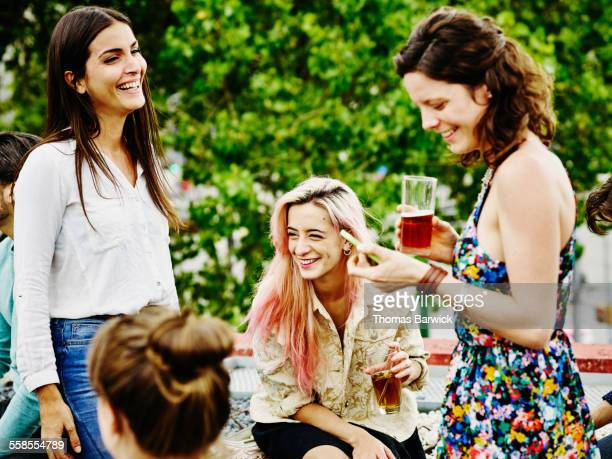 Female friends having drinks together during party