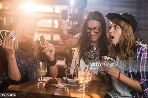 Female friends having fun in a cafe while playing cards.