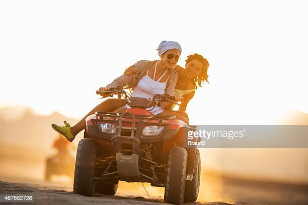 Female friends having fun while driving quad bike at sunset.