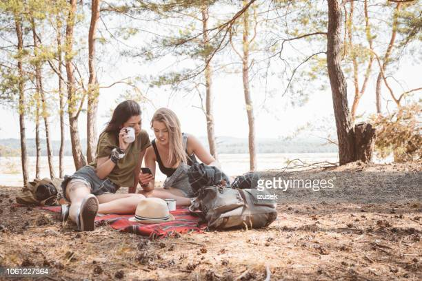 female friends having picnic in the forest - izusek stock pictures, royalty-free photos & images